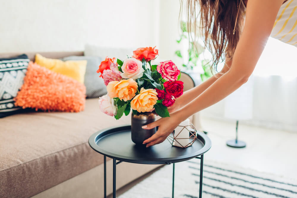 Woman putting vase of flowers on table
