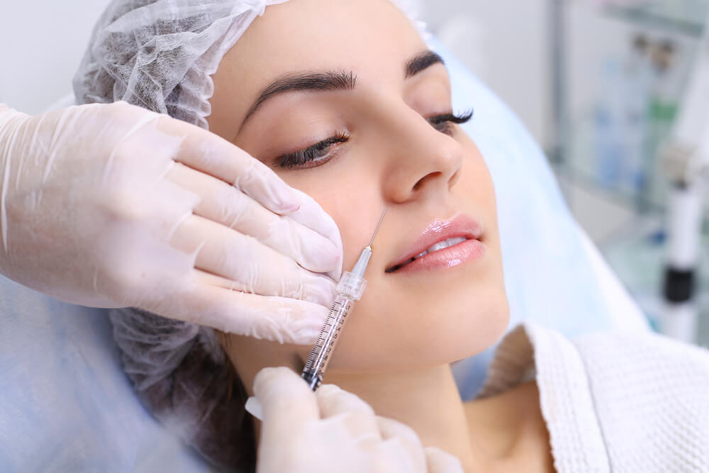 Woman having facial filler injected
