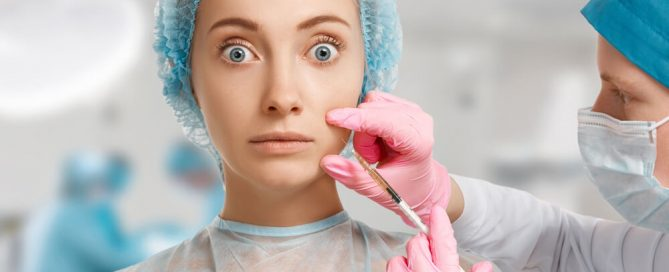 Woman in hospital with wide eyes as surgeon is injecting her face
