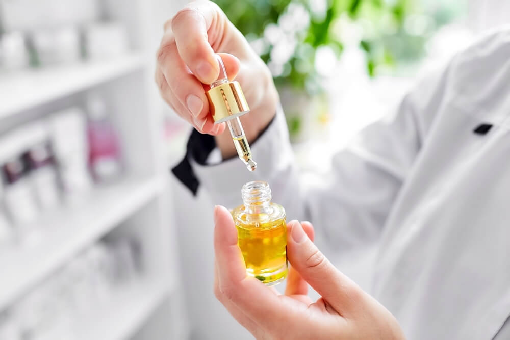 Hands holding vitamin C serum