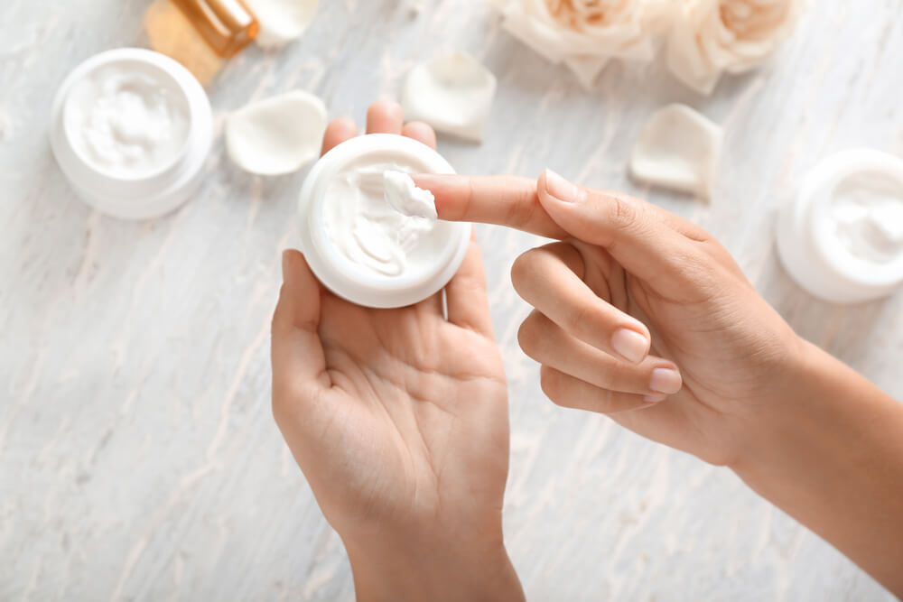 Person with finger in jar of skin cream