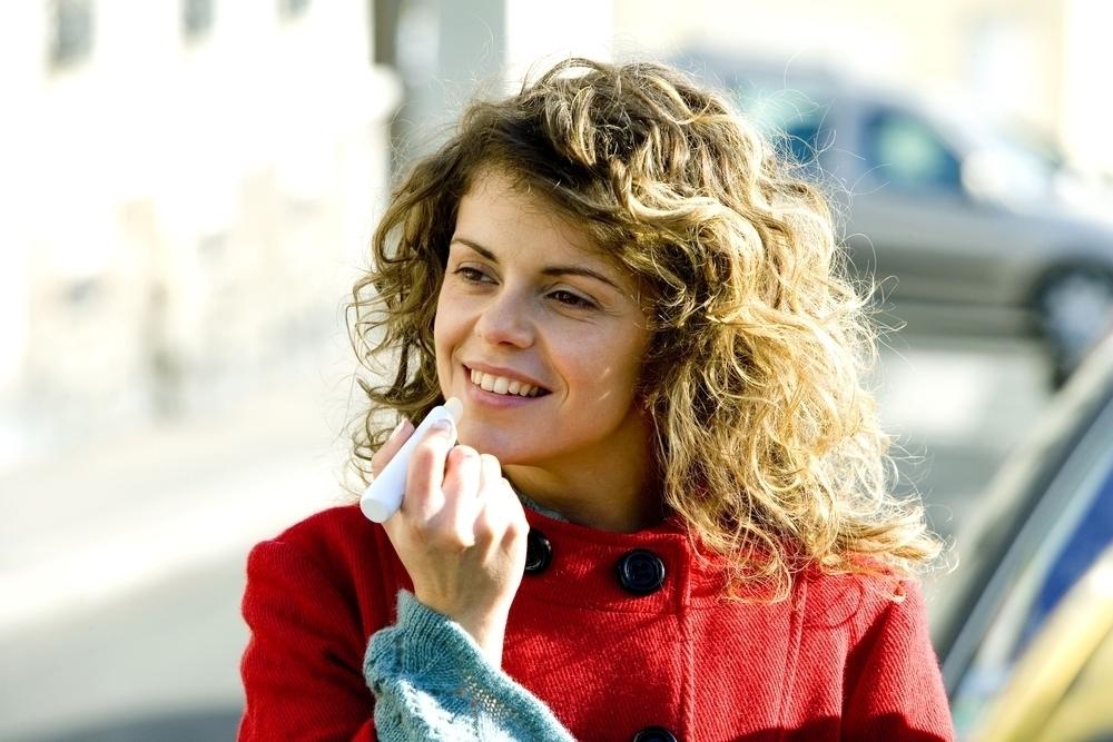 woman applying lip balm in red coat