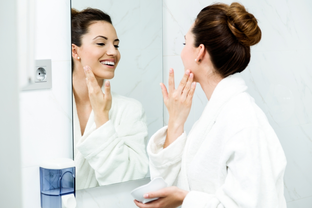 Woman applying skincare in the mirror