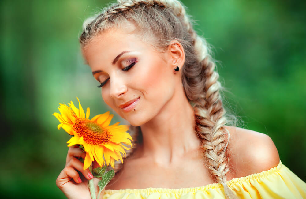 Pretty young woman with braids sniffing a sunflower