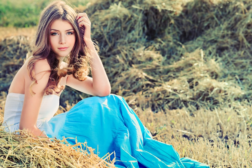 Pretty young woman sitting outdoors in a field