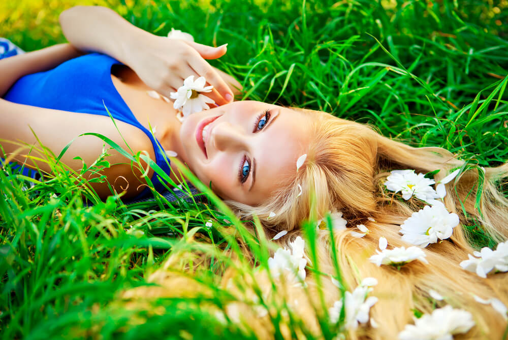 Woman with flowers in hair on grass