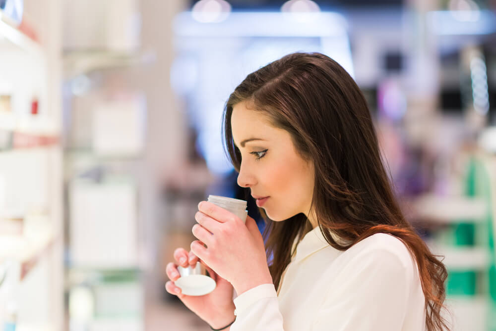 Woman sniffing skincare products at store