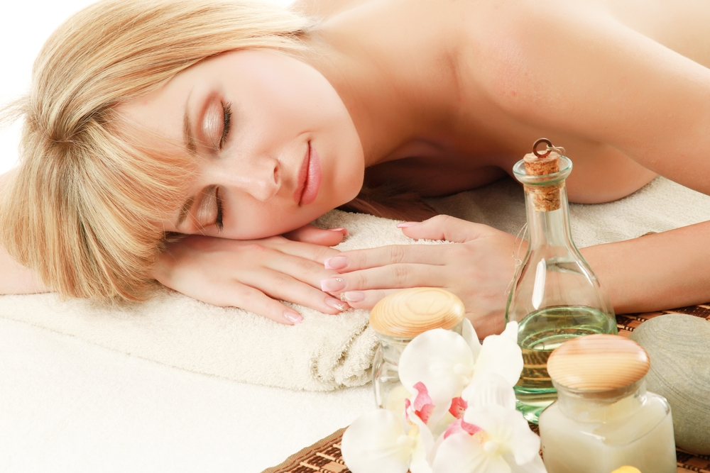 Woman at a spa surrounded by essential oils