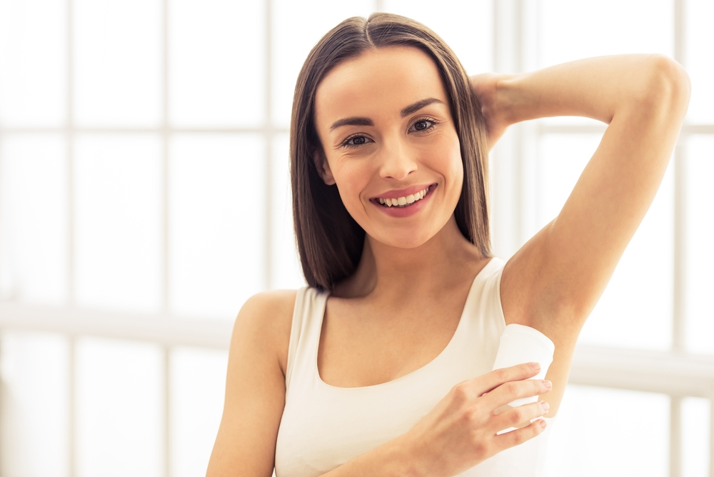 Woman applying deodorant on underarm